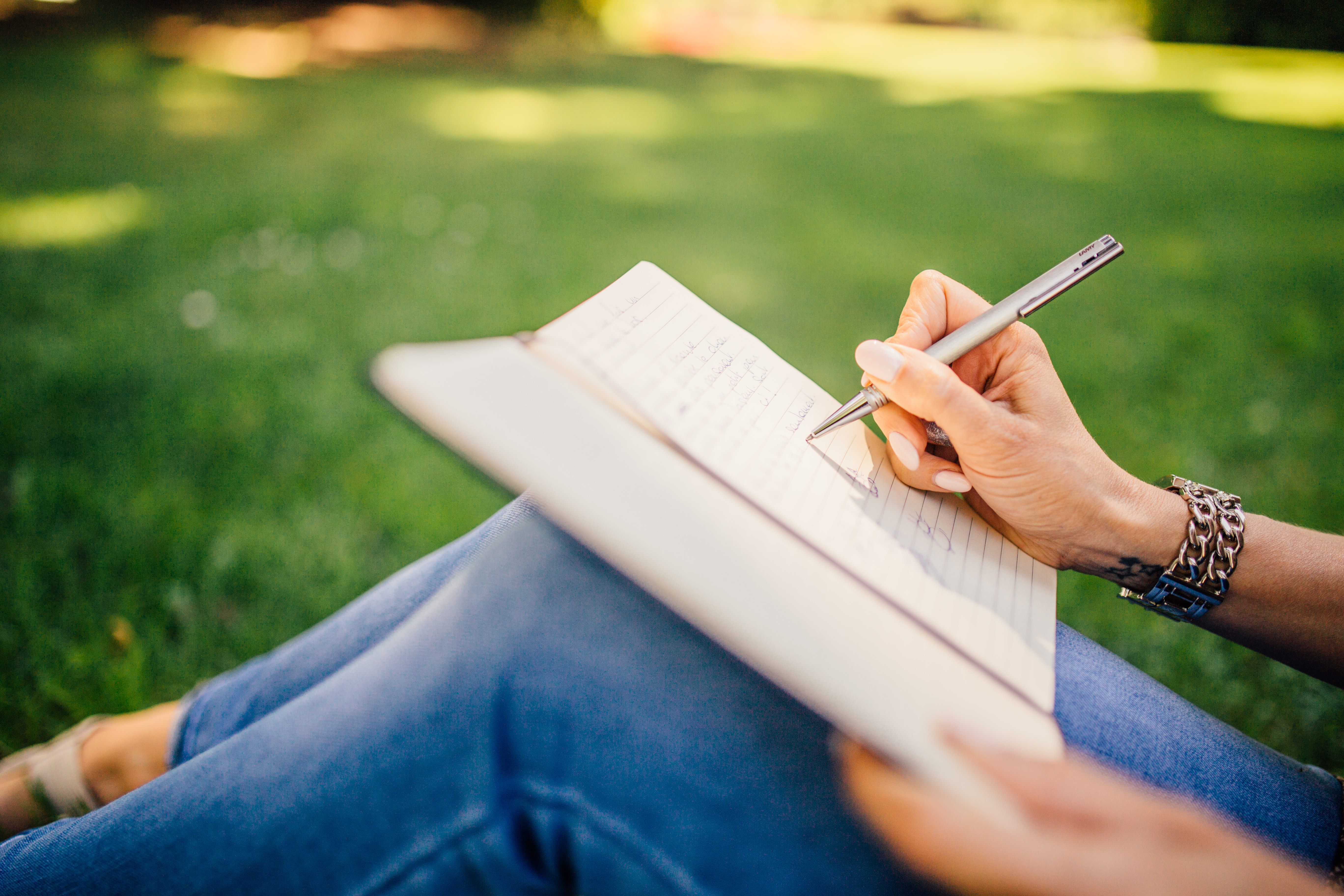Woman writing in a journal sitting on grass.